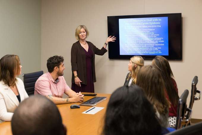 woman standing at the front of a meeting room pointing to a screen with  vague words on it. 5 people are sitting around a table looking at her and the screen